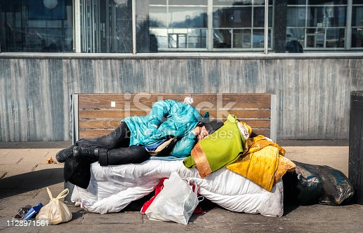istock Poor homeless man or refugee sleeping on the wooden bench on the urban street in the city with bags of clothes and junk on sunny cold day, social documentary concept 1128971561