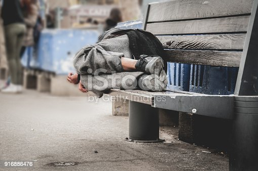 istock Poor homeless man or refugee sleeping on the wooden bench on the urban street in the city, social documentary concept, selective focus 916886476