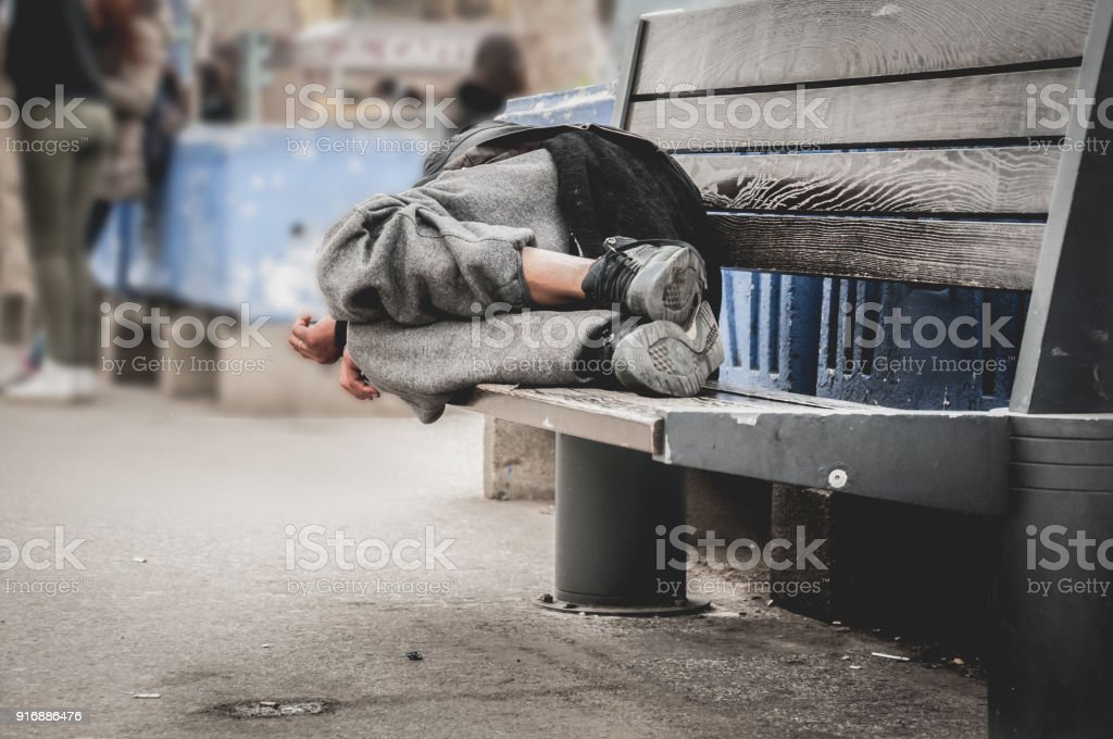Poor homeless man or refugee sleeping on the wooden bench on the urban street in the city, social documentary concept, selective focus stock photo