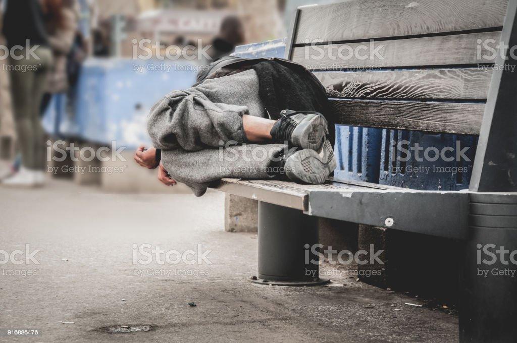 Pobre homem sem-teto ou refugiado dormindo no banco de madeira na rua urbana na cidade, conceito de documentário social, foco seletivo - foto de acervo