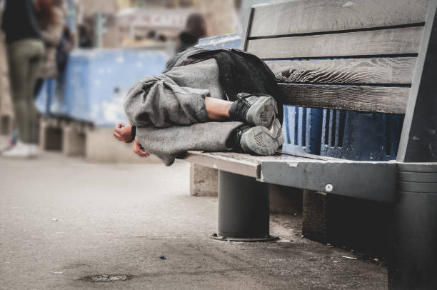 poor homeless man or refugee sleeping on the wooden bench on the urban street in the city, social documentary concept, selective focus - homelessness stock photos and pictures