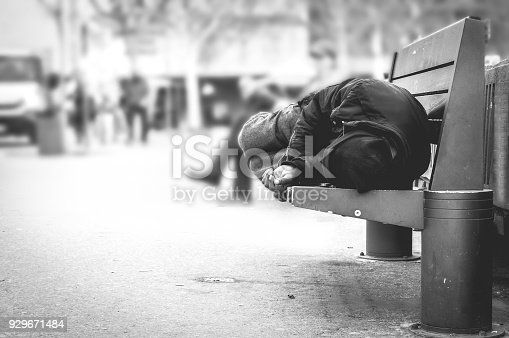 istock Poor homeless man or refugee sleeping on the wooden bench on the urban street in the city, social documentary concept, selective focus, black and white 929671484