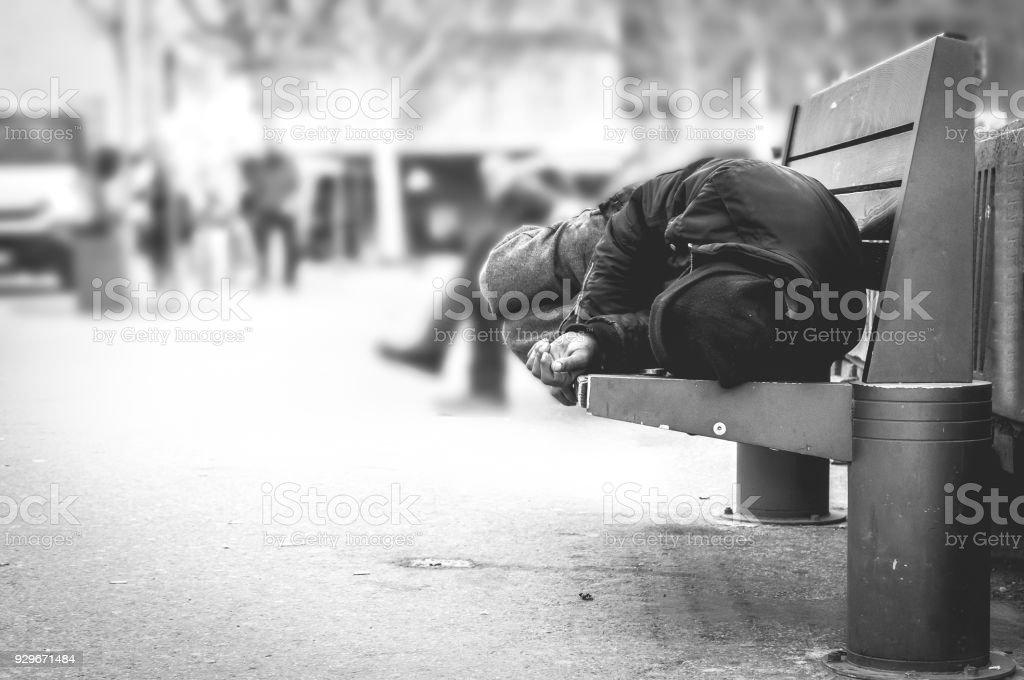 Pobre homem sem-teto ou refugiado dormindo no banco de madeira na rua urbana na cidade, conceito de documentário social, foco seletivo, preto e branco - foto de acervo