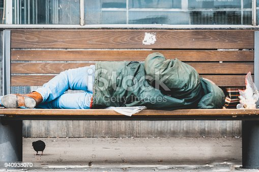 istock Poor homeless man or refugee sleeping on the wooden bench on the urban street in the city, social documentary concept 940938070
