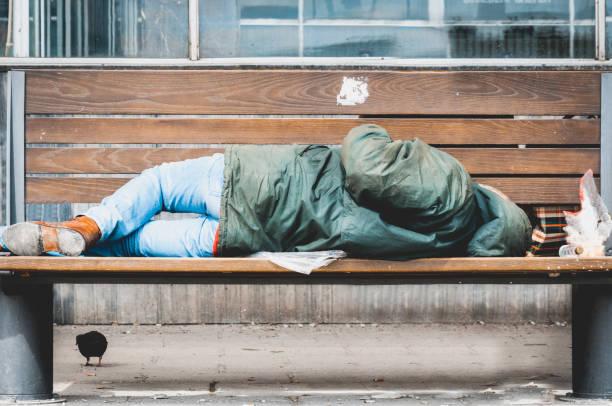 armen obdachlosen oder flüchtling schlafen auf der holzbank auf der städtischen straße in der stadt, soziale dokumentarische konzept - dokumentation stock-fotos und bilder
