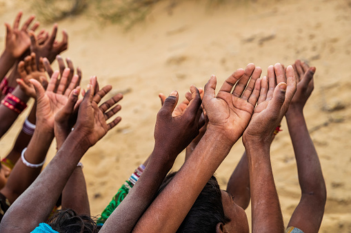 Poor Indian children keeping their hands up and asking for support. Many Indian children suffer from poverty - more than 50% of India's total population  lives below the poverty line, and more than 40% of this population are children.