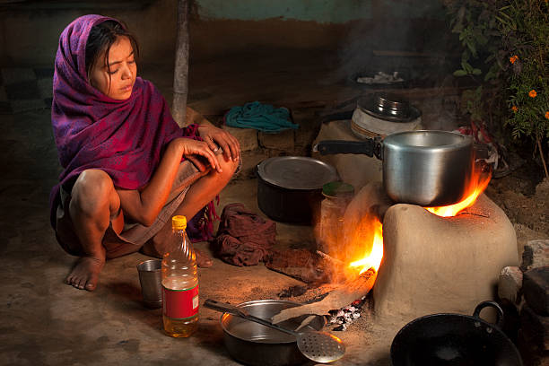 Poor, Indian girl cooking food on a clay stove stock photo