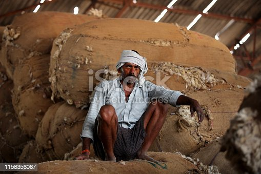 istock Poor Indian men in wool factory 1158356067