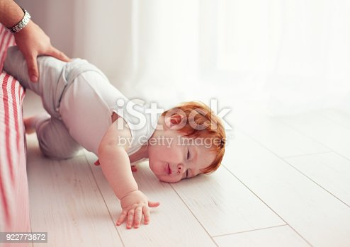 istock Poor little toddler baby fell down from the bed while crawling on it. Dad missed to catch him 922773672
