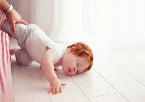 arme baby kleinkind fiel aus dem bett während kriecht auf sie. papa verpasst um ihn zu fangen - fails zum thema eltern stock-fotos und bilder