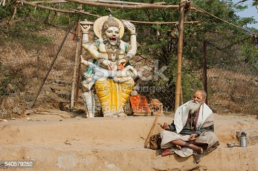 istock Poor man resting by sculpture of hindu god Narasimha 540579252