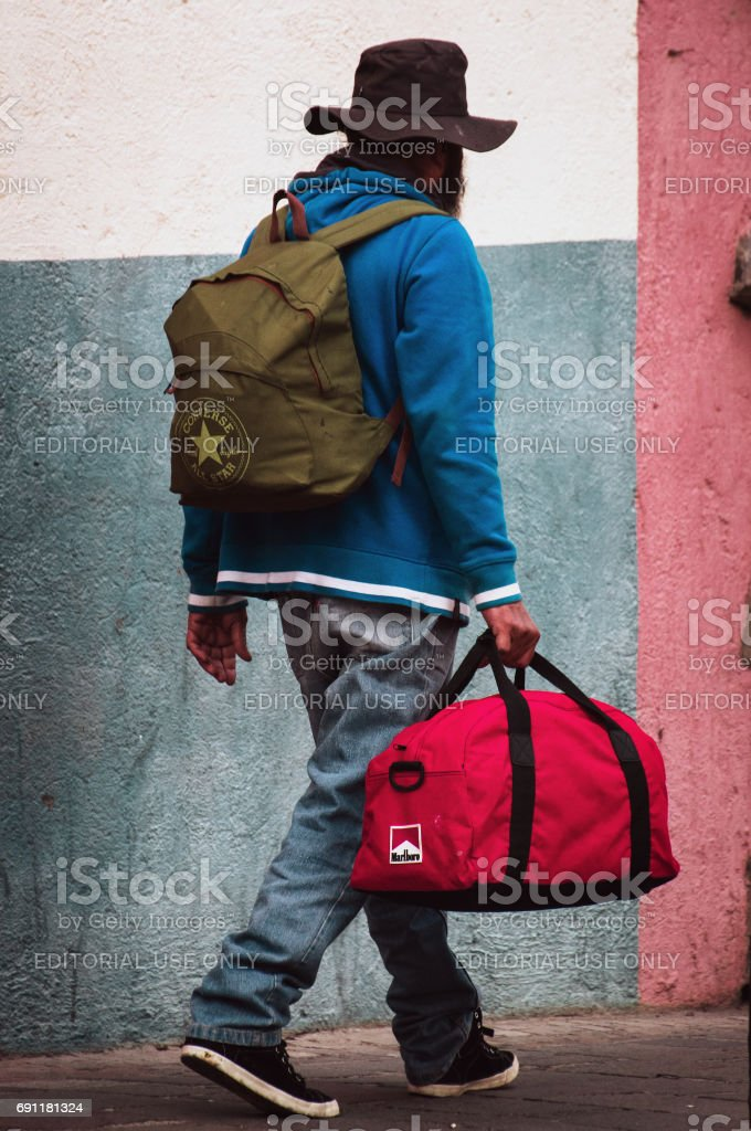 Poor man with rucksack and red bag is walking along the street. stock photo