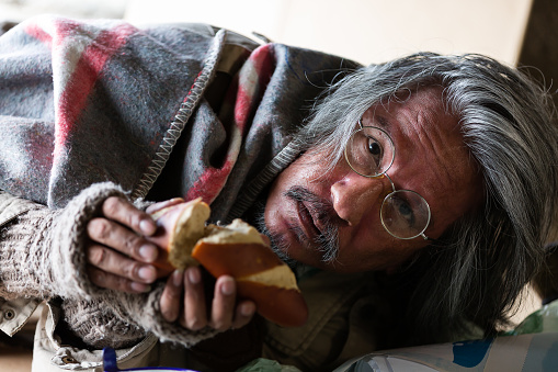 Poor old homeless asian man lying on street and holding bread, food and looking to the camera.