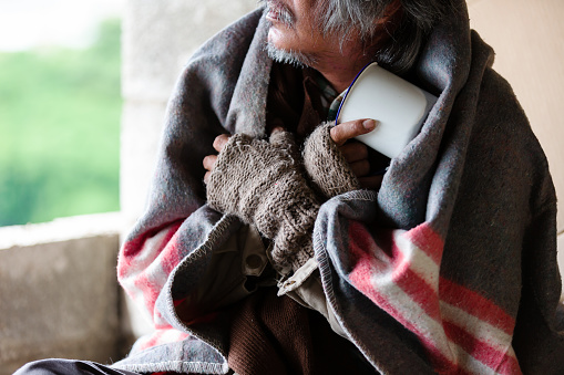 Poor old homeless asian man sitting with dirty blanket, gloves sitting cold in the corner of an abandoned building.