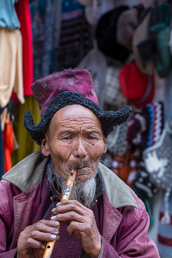 Leh, India - june 24, 2015 : Poor old man on the street market in mountain village Leh, Ladakh region, north India, close up. Poverty is a major issue in India