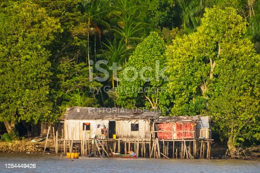 Belem, State of Para - August 9th, 2016 -  Woman puts clothes to dry on the clothesline and husband arrives by boat to the house. House located at the margi of Guamu River, near Belem, capital of the state of Para.