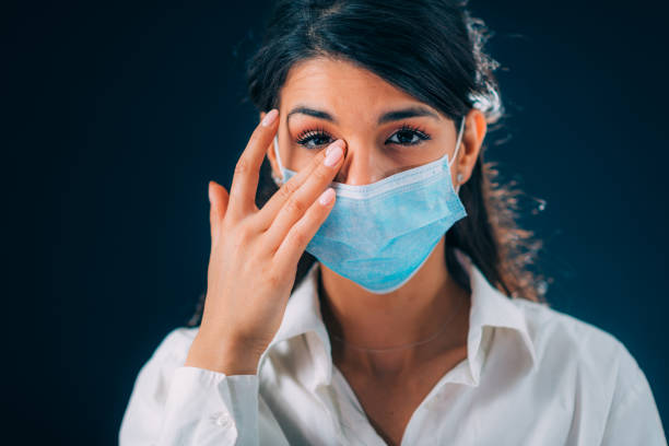 Poor Practices Against Corona Virus Infection. Beautiful Young Woman Touching Her Eyes stock photo