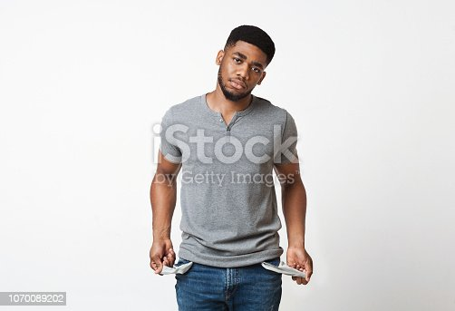 Poverty and absence of money. Unemployed sad african-american man showing empty pockets, white studio background