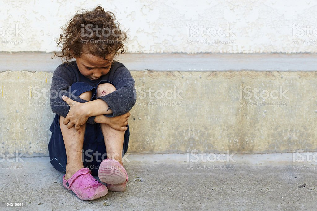 poor, sad little child girl sitting against the concrete wall stock photo