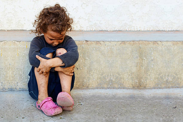 poor, sad little child girl sitting against the concrete wall - homelessness stock photos and pictures
