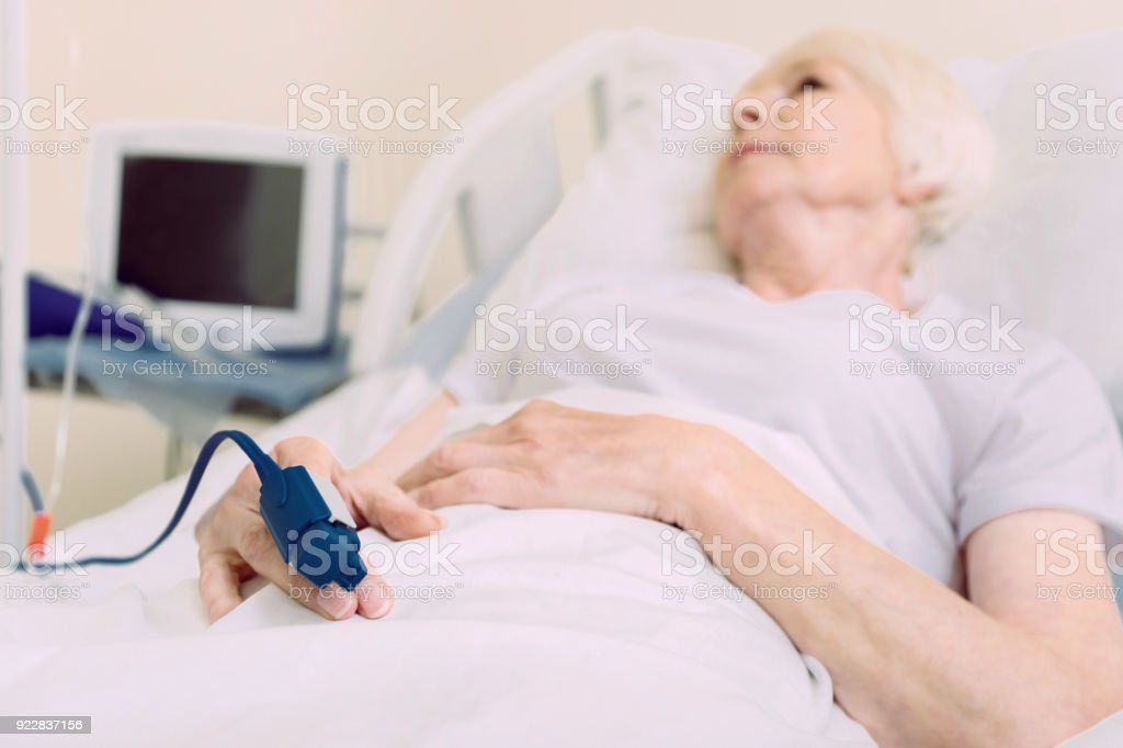 Poor Senior Lady Lying In Hospital Bed With Pulse Oximeter
