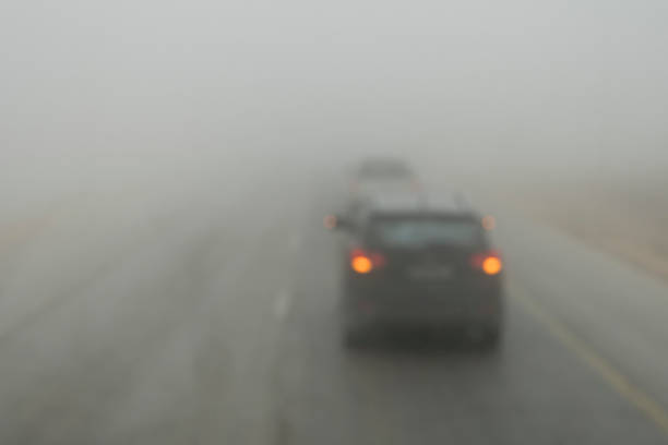 Poor visibility on the road. Fog early in the morning on the highway. slow-moving cars in heavy smoke from forest fires. Dangerous traffic. Bad weather. Slippery asphalt. driver's eyesight is poor stock photo