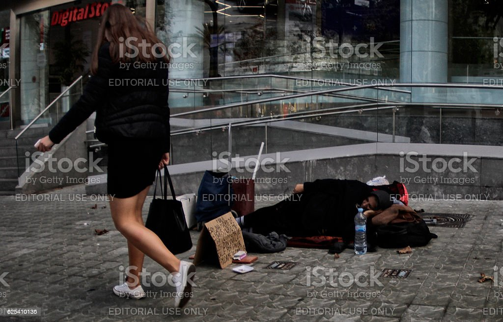 Poor woman asks for money in a commercial street in Barcelona stock photo