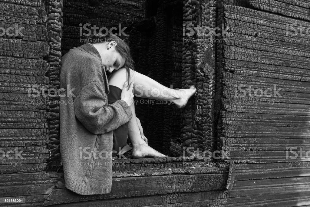 Poor woman in burnt house. Ditry legs. stock photo