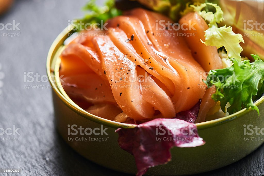Poorly salted salmon served in a tin and crispy baguette stock photo