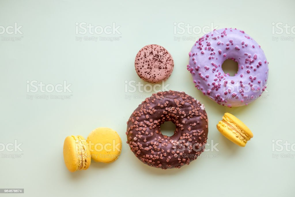 Pop Art Color style donuts, macarons and bakery goodies on bright colorful background.Minimalistic concept of donuts and french macaroons dessert.different pastel colors. glazed donuts with colorful sprinkles.Copy space royalty-free stock photo