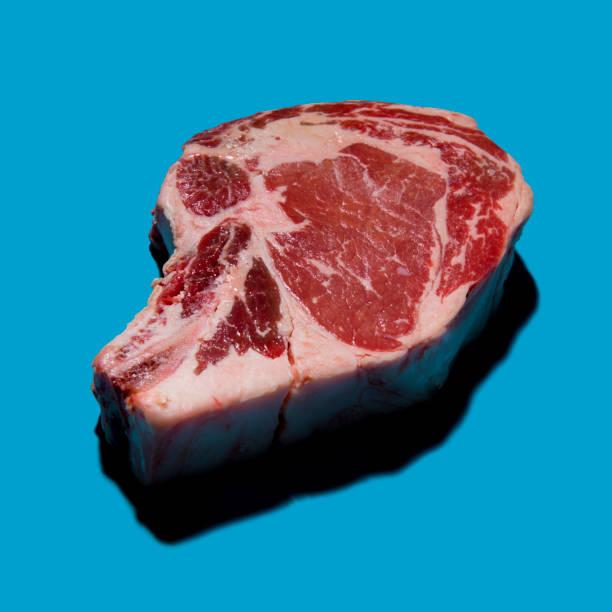 Pop Art Fleisch roh t-Bone Steak auf leuchtend blauem Hintergrund – Foto