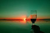 Pop art style hand holding wineglass against sunset over the mirror effect of Uyuni Salt Flats, Bolivia