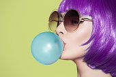 Pop art woman portrait blowing a blue bubble chewing gum