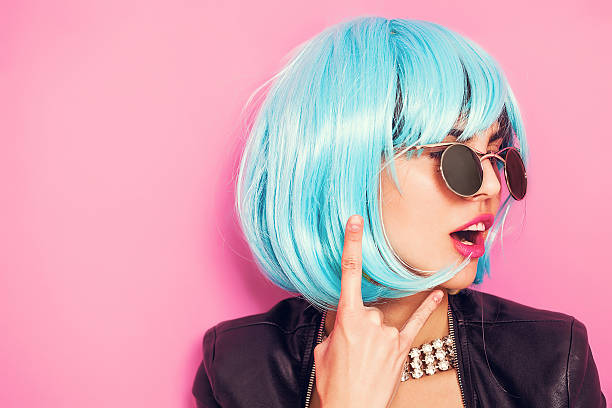 Pop girl portrait wearing blue wig and making the horns stock photo