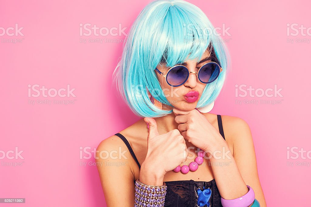 Pop girl portrait with thumbs up wearing weird accessories stock photo
