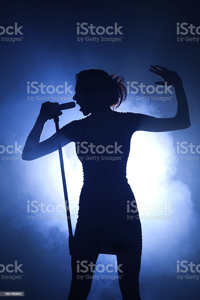 Pop idol backlit with microphone on the big stage royalty-free stock photo