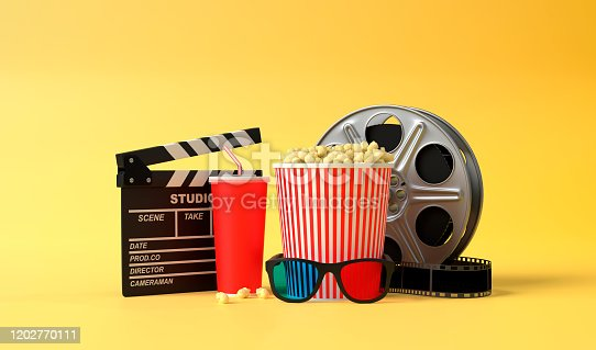 956942702 istock photo Popcorn, 3D glasses, disposable cups of red cola, film reel and clapboard on a yellow background 1202770111