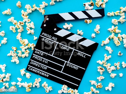 istock Popcorn and clapperboard on blue background. the concept of movie, film, entertainment, advertising 955488882