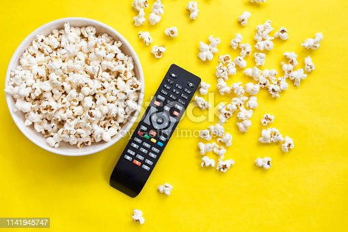 Popcorn and remote control viewed from above on yellow background. Flat lay of pop corn bowl. Top view
