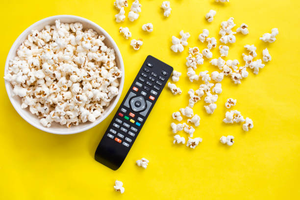 Popcorn and remote control viewed from above on yellow background. Flat lay of pop corn bowl. Top view Popcorn and remote control viewed from above on yellow background. Flat lay of pop corn bowl. Top view remote control stock pictures, royalty-free photos & images
