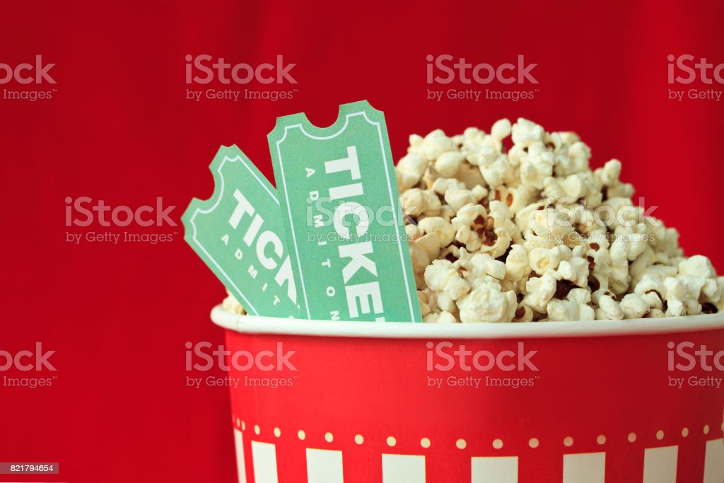 Popcorn Bag And Movie Ticket On Red Background stock photo