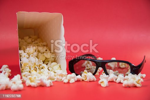 956942702 istock photo popcorn box full of popcorn with spread popcorn and 3d black cinema glasses on vibrant Red background Film Movie background 1192232768