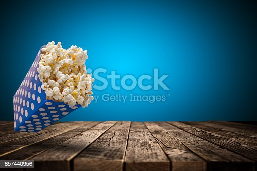 istock Popcorn box on old wooden table 857440956