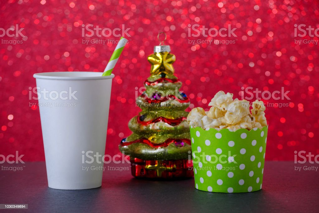 popcorn, drink and christmas tree decoration for movie on red bokeh background, selective focus stock photo