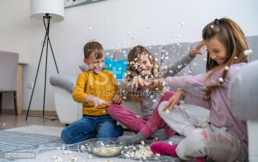 Triplets are playing with popcorn in living room
