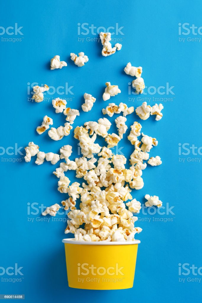Popcorn. Flat lay of popcorn cup on a blue background. Top view stock photo