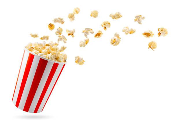 popcorn vliegt uit een volle emmer close-up op een witte. geïsoleerd. - popcorn stockfoto's en -beelden