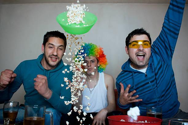 popcorn flying all over the place - football friends tv night stockfoto's en -beelden