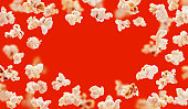 Popcorn frame with space for text, flying popcorn isolated on red background with copy space, movie poster concept