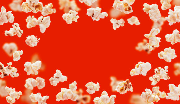 Popcorn frame, flying popcorn isolated on red background with copy space, movie poster concept stock photo
